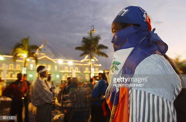 Haitian man wrapped in a haitian flag watches as others take part in the annual carnival celebration in front of the Presidential palace in...