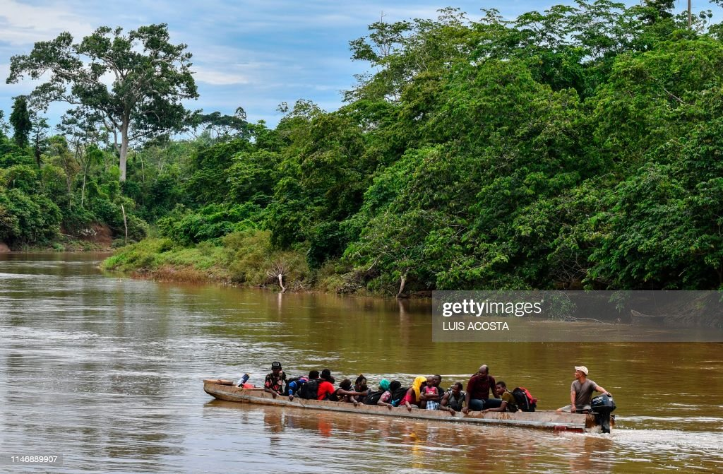 Haitian migrants cross the Chucunaque River by boat to the