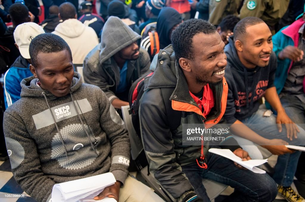 haitian migrants wait to be assisted with procedures and