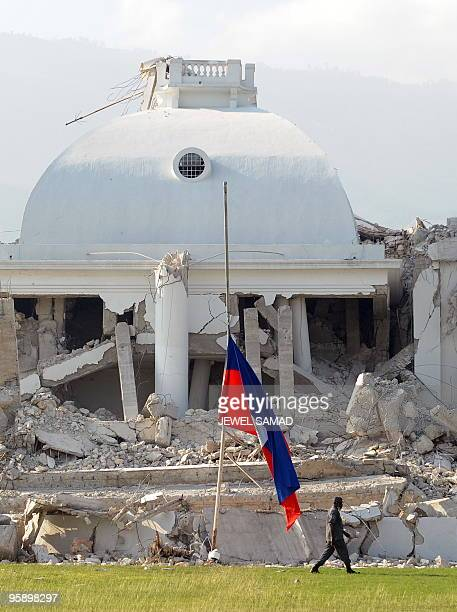 A Haitian national flag flies half mast at the collapsed presidential palace as a soldier patrols in PortauPrince on January 20 2010 after the...