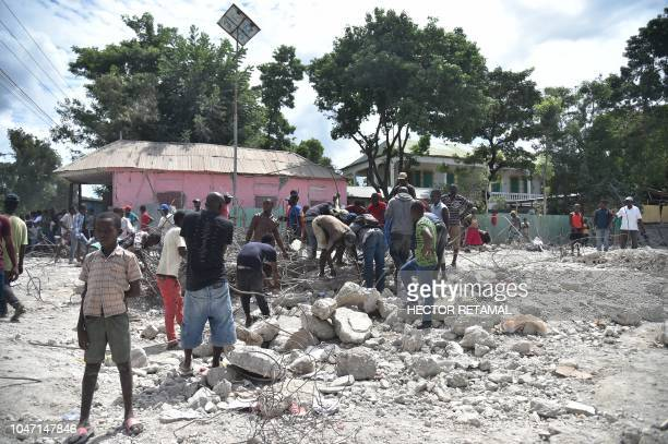 Haitian people collect metal on October 7 2018 in Gros Morne Haiti from the destroyed auditorium after the earthquake that struck north of Haiti on...