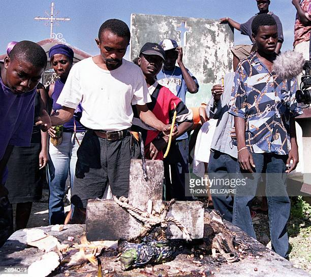 """Haitian people conduct prayers to """"Baron Samedi"""", or the voodoo god of the death, 01 November 2003 at the Petion-ville cemetery in Port-au-Prince...."""