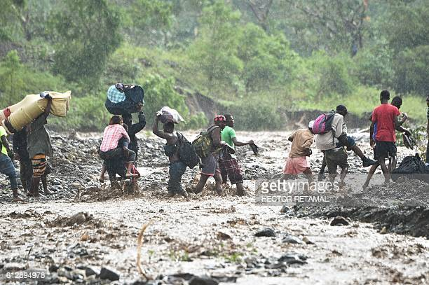 TOPSHOT Haitian people cross the river La Digue in Petit Goave where the bridge collapsed during the rains of the Hurricane Matthew southwest of...
