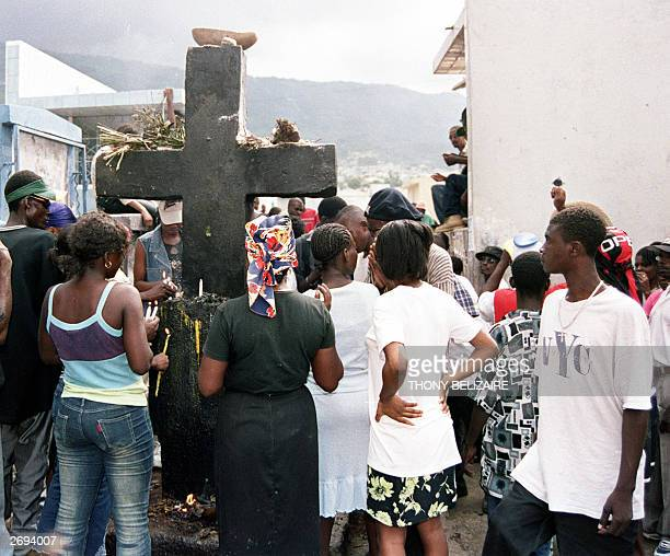 Haitian people offer food and drinks to the black cross, representating Baron Samedi or god of death in Haitian Voodoo, 01 November 2003 at the main...