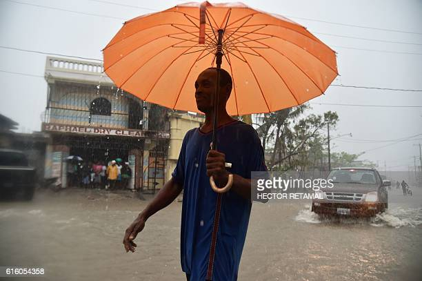 TOPSHOT Haitian people travel in a flooded street through the rain during a tropical storm in the commune of Les Cayes Haiti on October 21 2016 At...
