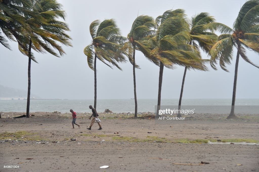 TOPSHOT - Haitian people walk through the wind and rain on a