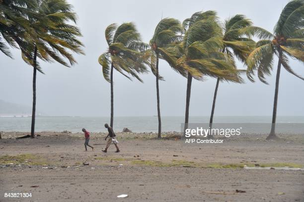 TOPSHOT Haitian people walk through the wind and rain on a beach in CapHaitien on September 7 as Hurricane Irma approaches Irma was packing maximum...