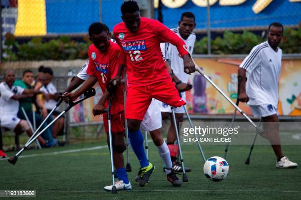"""Haitian player controls the ball during a friendly football match called """"Two Crutches and a Ball"""" against Dominican Republic in commemoration of the..."""
