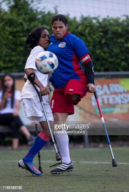 """Haitian player vies for the ball with a Dominican player during a friendly football match called """"Two Crutches and a Ball"""" in commemoration of the..."""