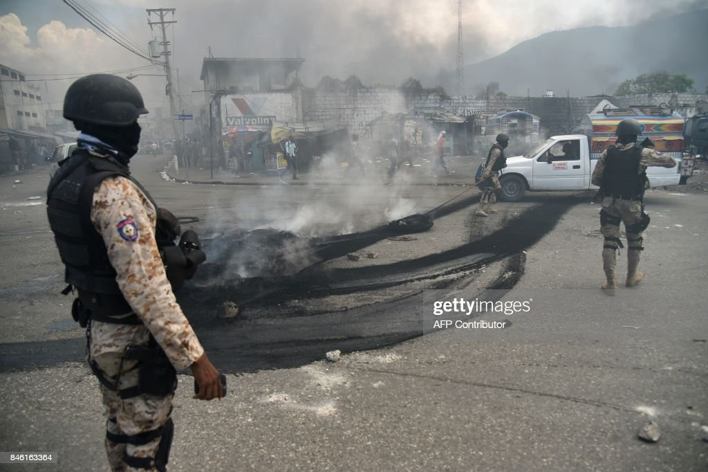 Haitian police extinguish burning tires placed by demonstrators during an anti-government protest in the centre of the Haitian capital Port-au-Prince, on September 12, 2017. Demonstrators took to the streets to protest against the government and the new budget for 2017-2018, throwing stones at the police, setting tires on fire and blocking some streets. /