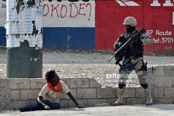 Haitian police officer inspect a man nearby the International Airport in PortauPrince on February 15 on the ninth day of protests against Haitian...