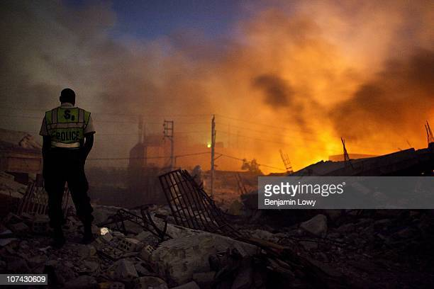 Haitian police officer watches a fire rage through earthquake ravaged downtown Port au Prince, Haiti. On January 12, 2010 Haiti was struck by a...