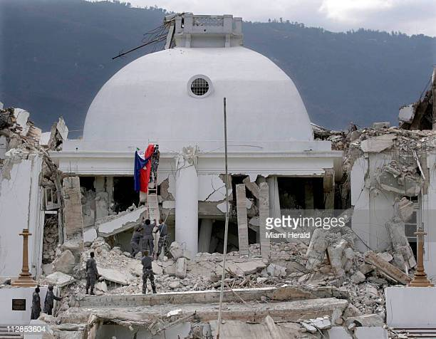 Haitian Police officers take down the flag that had been draped near the top of the National Palace in PortauPrince Haiti Sunday January 17 2010...