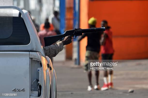 Haitian police prepares to fire teargas to demonstrators during clashes in PortauPrince on February 15 on the ninth day of protests against Haitian...