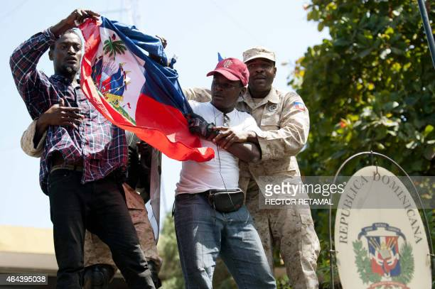Haitian police remove protestors who tried to place the Haitian flag on the mast of the Consulate General of the Dominican Republic during a...