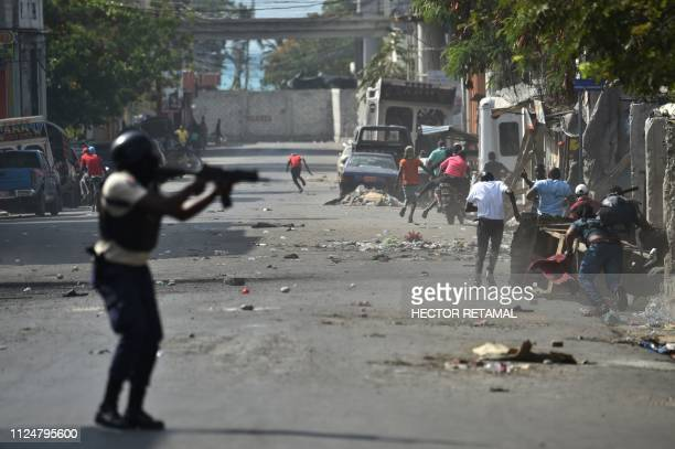 Haitian police shoot their weapon while pursuing demonstrators during the clashes in the centre of Haitian Capital PortauPrince on February 13 2019...