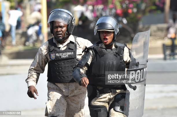 A Haitian policeman helps his colleague who was injured during clashes with demonstrators near the National Palace in the centre of Haitian Capital...