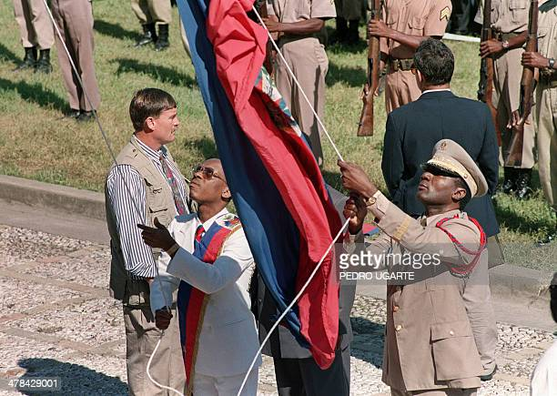 Haitian President JeanBertrand Aristide and Haiti's interim Army Chief JeanClaude Duperval surrounded by bodyguards hoist the Haitian flag outside...