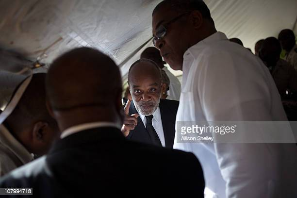 Haitian President Rene Preval speaks with men including Haitian Prime Minister JeanMax Bellerive under a tent before a service to commemorate those...