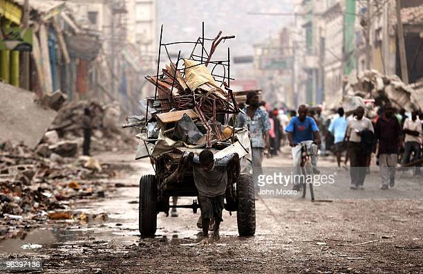 Haitian pulls a load of salvaged metal from earthquake rubble on February 3, 2010 in Port-au-Prince, Haiti. An estimated three million Haitians have...