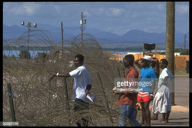 Haitian refugees picked up at sea by Coast Guard, seeking US asylum, at US naval base camp, detained pending US court ruling on repatriation.