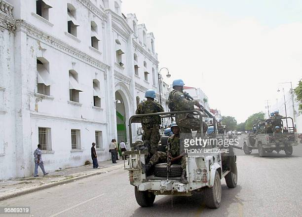 Haitian residents walk in the streets under the watch of Brazilian UN troops patrolling the street as a part of a major peacekeeping operation in Bel...