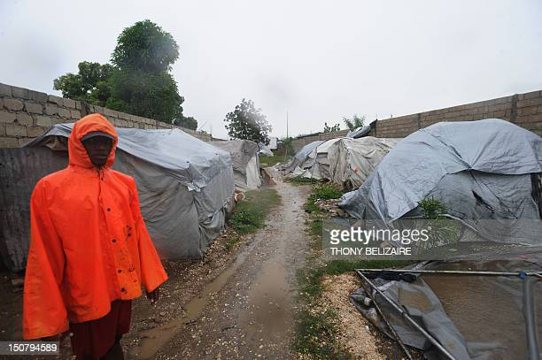A Haitian stands amid tents in a camp as Tropical Storm Isaac barrels through PortAuPrince Haiti August 25 2012 Forecasters earlier said Isaac was...