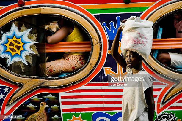 A Haitian street vendor offers water to the taptap passengers on the street of PortauPrince Haiti 26 July 2008 Taptap vehicles serve as public...