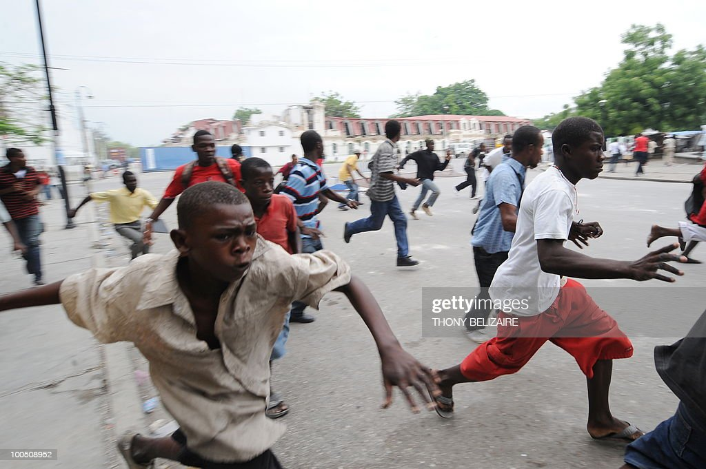 Haitian students run as they demonstrate on May 25, 2010 near the presidential palace in Port-au-Prince against alleged violence by UN peacekeepers against Haitian students on May 24. The students demanded the UN leave Haiti. AFP PHOTO/Thony BELIZAIRE