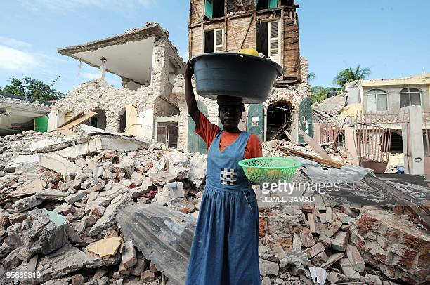 A Haitian vendor walks past a collapsed building in Jacmel on January 19 2010 a week after the country was shattered by a massive 70magnitude quake...
