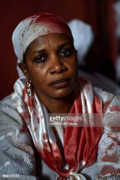 A Haitian voodoo follower wearing white clothes covered with the blood of sacrificed animals is seen during a voodoo ceremony in Souvenance a suburb...