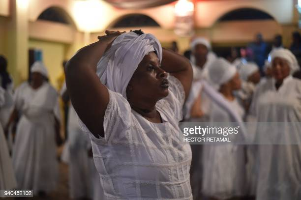 Haitian voodoo followers wearing white clothes participate in a voodoo ceremony in Souvenance a suburb of Gonaives 171km north of PortauPrince on...