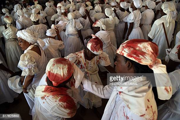Haitian voodoo followers with blood covered clothes from an animal sacrifice dance while taking part in the annual voodoo ceremony held during Easter...