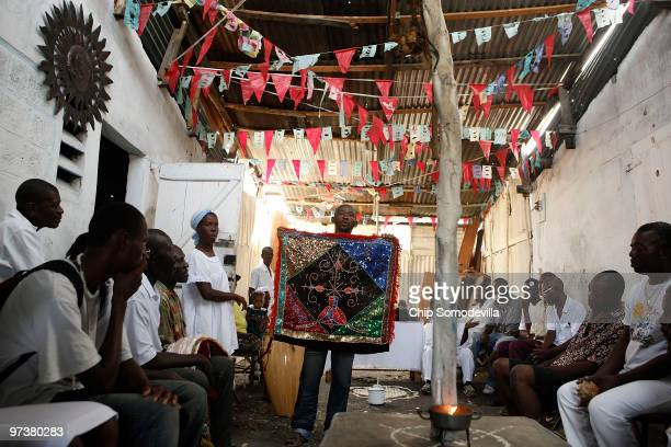 Haitian Voodoo priest or houngan Jul Mis holds a Voodoo flag decorated with rinestones and sequins during a ceremony in a 40yearold temple March 2...