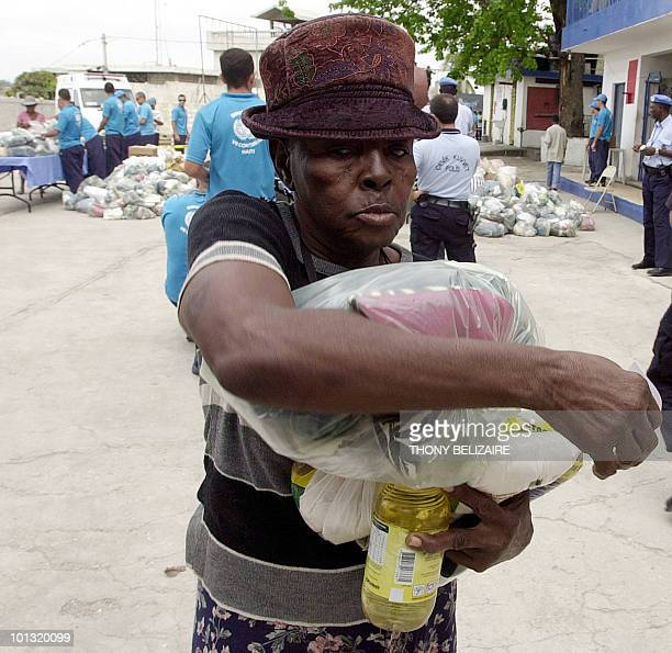 A Haitian woman carries food and clothes distributed by Brazilian UN Peacekeepers in PortauPrince on April 17 2008 Last weekend Haiti's premier was...