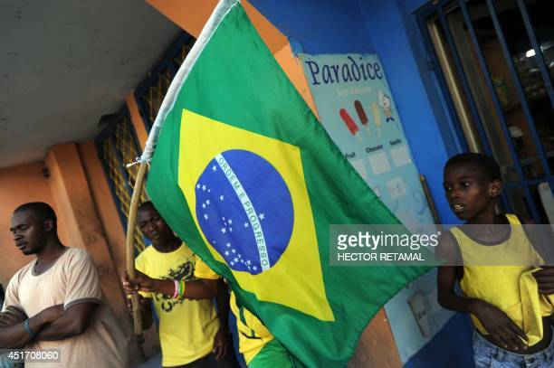 A Haitian woman holds a Brazilian flag while celebrating the triumph of Brazil vs Colombia during quarterfinal match in the World Cup Brazil 2014 in...
