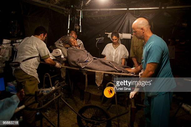 Haitian woman is transfered out of the recovery room a day after she underwent surgery at the Israeli army hospital on January 19, 2010 in...