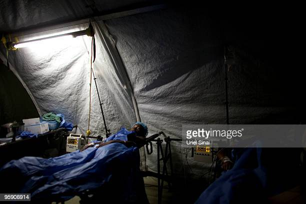 Haitian woman lays in the recovery room in the Colombian hospital January 20, 2010 in Port-au-Prince, Haiti. Aid has started trickling out to...