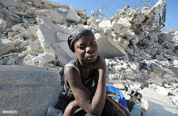 Haitian woman rests siting on the rubbles of a destroyed building at a market in Port-au-Prince on January 22, 2010 following the massive...