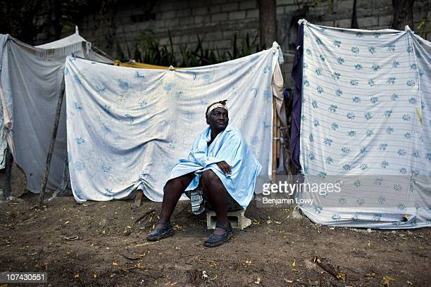 Haitian woman sits outside her waterlogged tent that was damaged, along with her few remaining belongings, following an early morning rainstorm that...