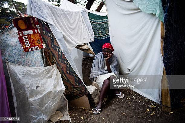 Haitian woman sits outside her waterlogged tent that was damaged, along with her few remaining belongings, and worries about her sick 1 year old...
