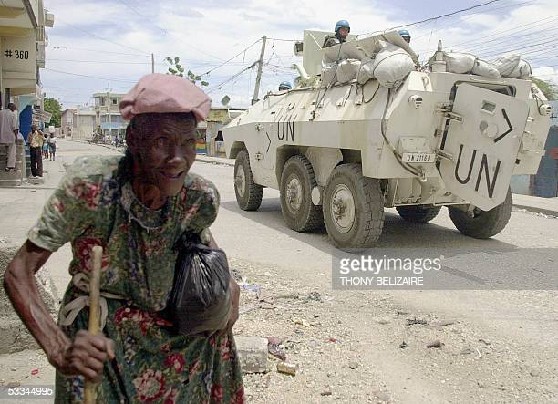 Haitian woman walks past a UN armored vehicle 08 August 2005 patrolling a street as a part of a major peacekeeping operation in Bel Air a slum that...