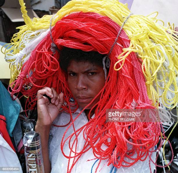 A Haitian woman wears a bundle of multicolored ropes on her head as she sells them 27 April 2000 in a public market in PortauPrince AFP PHOTO/THONY...