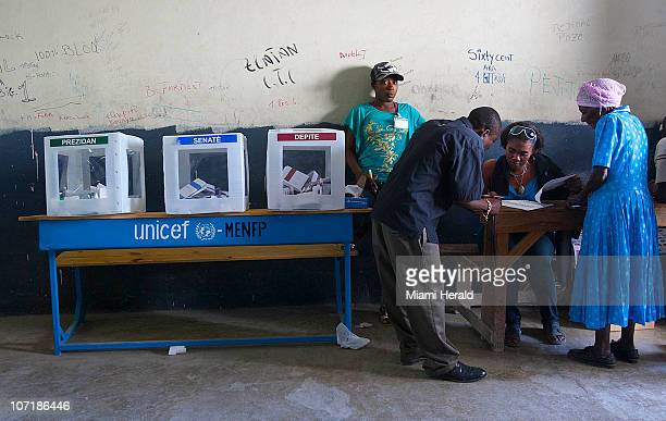 Haitian women check for a name at a local school in PortauPrince Haiti during voting presidential election on Sunday November 28 2010