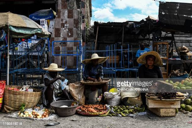 Haitian women sell fruits and vegetables at a local market in PortauPrince on January 23 2020