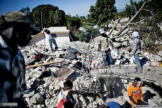 Haitian workers search through the rubble of a destroyed home for the remains of its owners. On January 12, 2010 Haiti was struck by a magnitude 7...