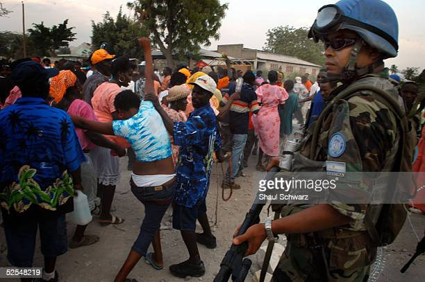 Haitians attending a rara march through the city walk past a UN peacekeeper March 26 2005 in Gonaives Haiti Every year during the week of Good Friday...