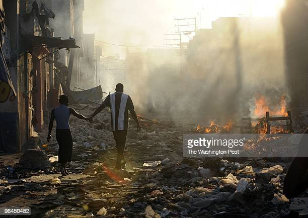 Haitians burn debris from the earthquake damage as people take goods from destroyed stores in the marketplace on January 18 2010 PortauPrince Haiti
