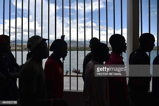Haitians deported from the Dominican Republic wait as they are transferred across the border by Dominican migration authorities in Malpasse on...