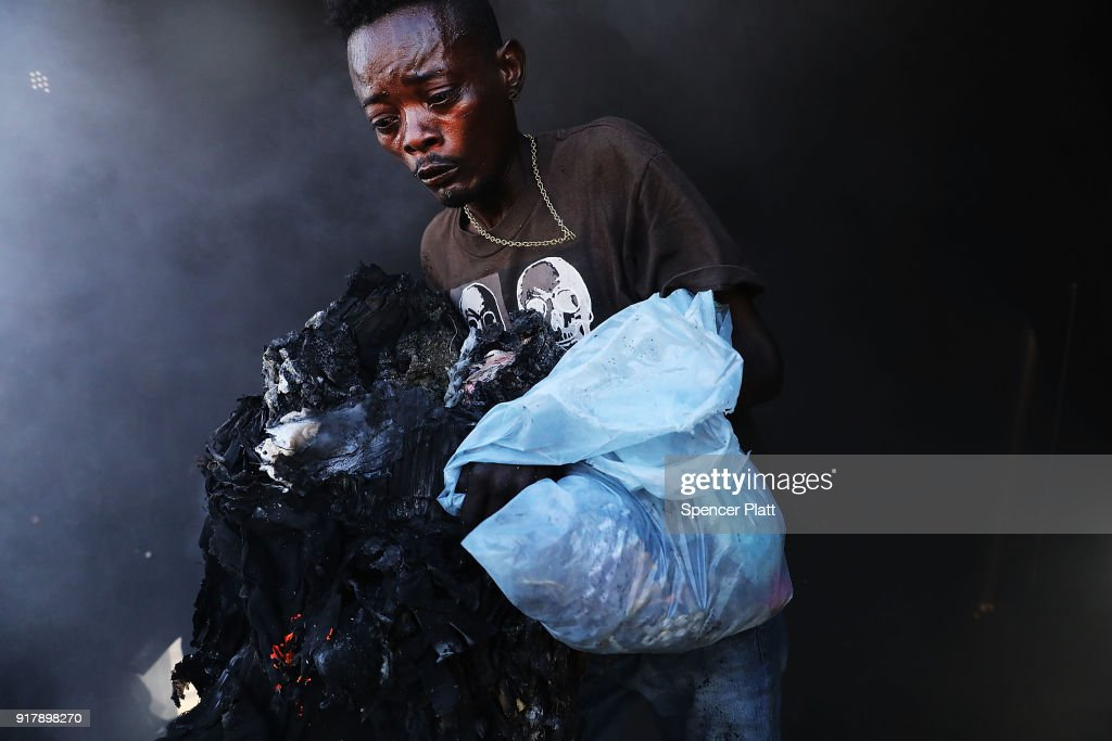Haitians desperately try to get into a burning shipping container to salvage clothes during a fire at Port-au-Prince's historic Iron Market on February 13, 2018 in Port-au-Prince, Haiti. Hundreds of locals vendors lost all of their merchandise in the early morning blaze which is still under investigation. Haiti, the poorest country in the Western Hemisphere, is still reeling from President Donald Trump's comments about the Caribbean nation and his decision to revoke Temporary Protected Status (TPS) for Haitians living in America following the 2010 earthquake that claimed over 300,000 lives. Haiti is currently preparing for the start of Carnival on Sunday.